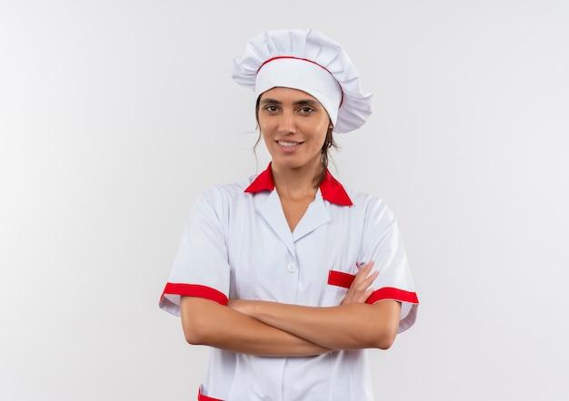 Uśmiechnięta młoda kobieta kucharz ubrana w mundur szefa kuchni skrzyżowania rąk z miejsca na kopię