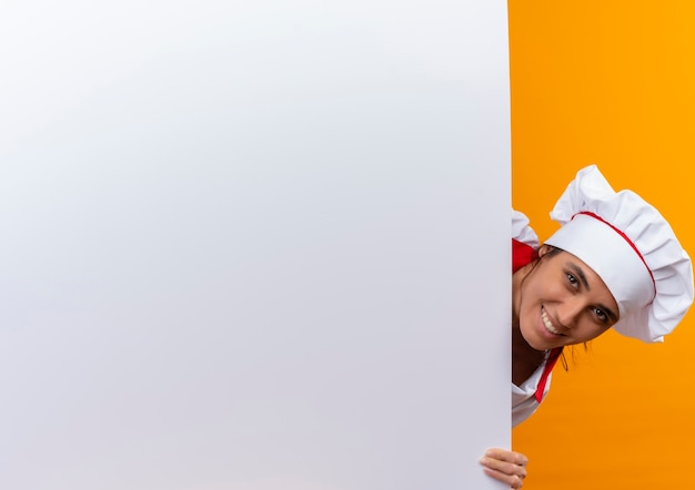 Uśmiechnięta młoda kobieta kucharz ubrana w mundur szefa kuchni trzyma białą ścianę z miejsca na kopię