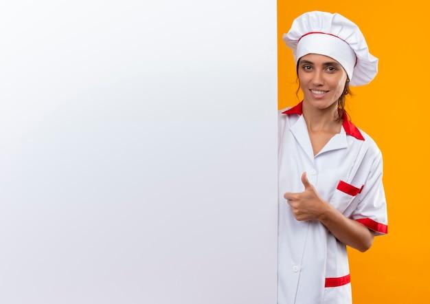 Uśmiechnięta młoda kobieta kucharz ubrana w mundur szefa kuchni trzymając białą ścianę jej kciuk z miejsca na kopię