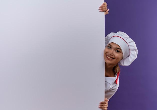 Uśmiechnięta młoda kobieta kucharz ubrana w mundur szefa kuchni trzymając białą ścianę na na białym tle z miejsca na kopię