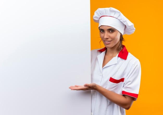Uśmiechnięta młoda kobieta kucharz ubrana w mundur szefa kuchni trzymając i pokazując ręką białą ścianę z miejsca na kopię