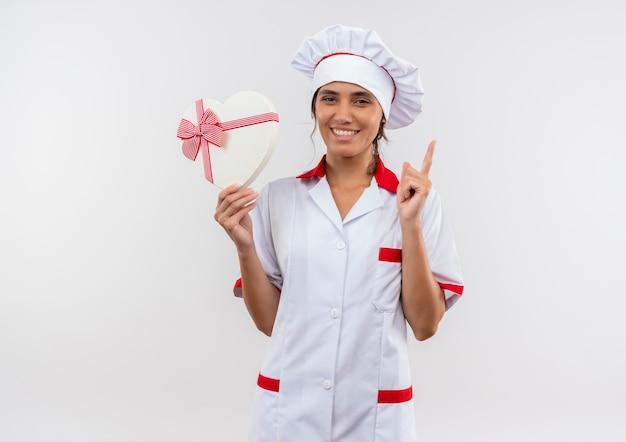 Uśmiechnięta młoda kobieta kucharz ubrana w mundur szefa kuchni trzymając pudełko w kształcie serca i wskazuje do góry z miejsca na kopię