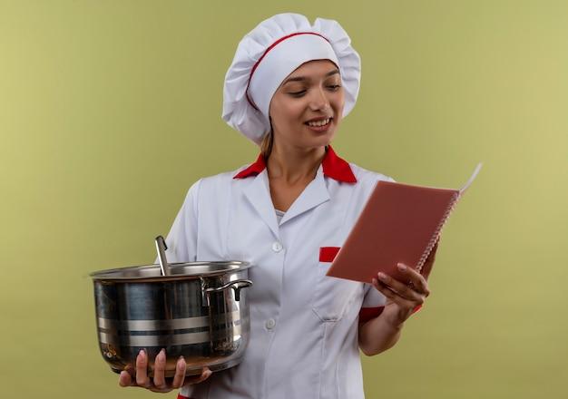 Uśmiechnięta młoda kobieta kucharz ubrana w mundur szefa kuchni trzymając rondel i patrząc na notebook w dłoni