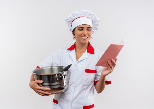 Uśmiechnięta młoda kobieta kucharz ubrana w mundur szefa kuchni trzymając rondel i patrząc na notebook w ręku z miejsca na kopię