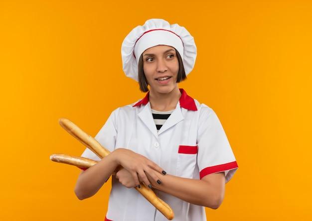 Uśmiechnięta młoda kobieta kucharz w mundurze szefa kuchni trzymając paluszki, patrząc na bok na białym tle na pomarańczowej ścianie