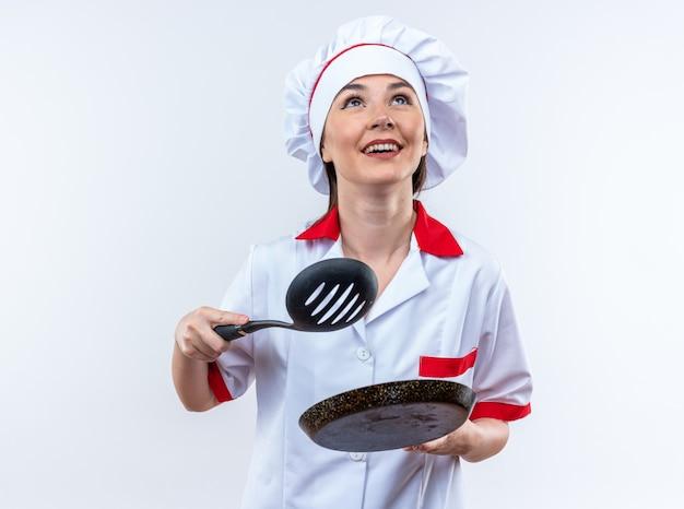 Uśmiechnięta młoda kobieta kucharz w mundurze szefa kuchni trzymająca szpatułkę z patelnią odizolowaną na białej ścianie