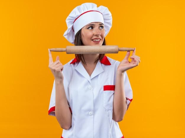 Uśmiechnięta młoda kobieta kucharz w mundurze szefa kuchni trzymająca wałek do ciasta na białym tle na pomarańczowym tle