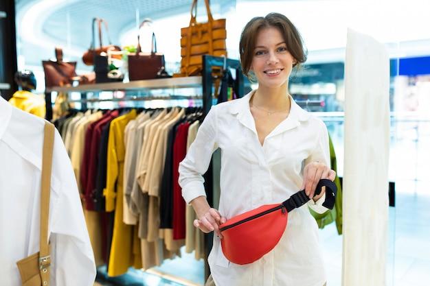 Uśmiechnięta młoda kobieta kupuje czerwoną pasek torbę przy butikiem na sprzedaży