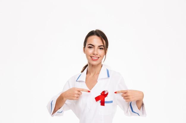 Uśmiechnięta młoda kobieta lekarz ubrany w mundur z czerwoną wstążką stojący na białym tle nad białą ścianą