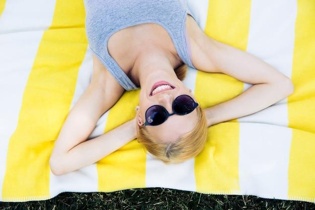 Uśmiechnięta młoda kobieta leżąca na macie