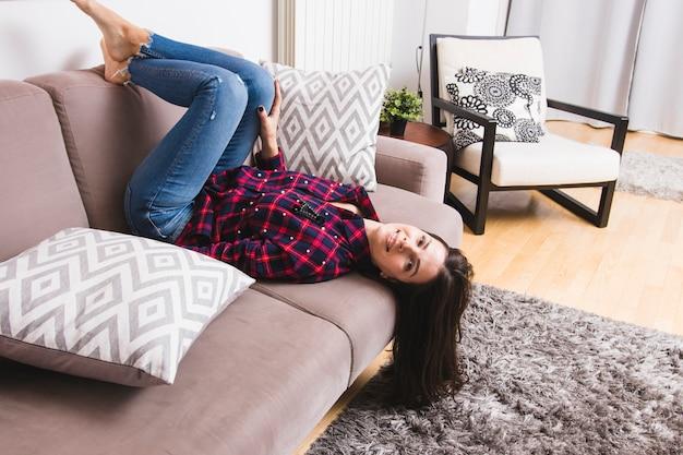 Uśmiechnięta młoda kobieta leży do góry nogami na kanapie w salonie