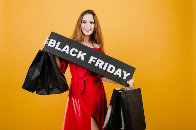 Uśmiechnięta młoda kobieta ma czarny piątek znak z papierowymi torbami na zakupy odizolowywającymi nad kolorem żółtym