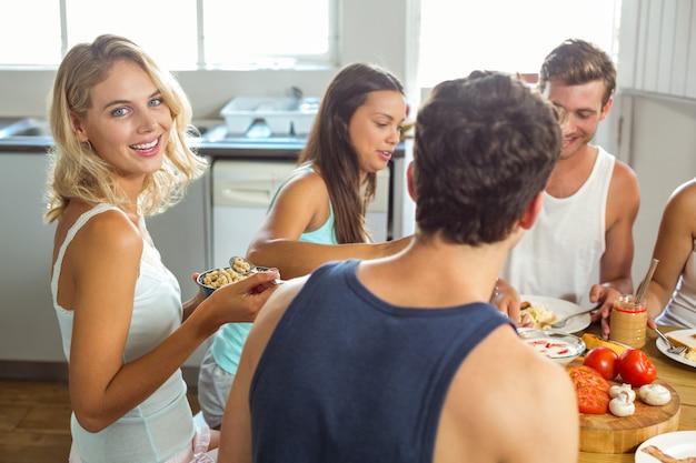 Uśmiechnięta młoda kobieta ma śniadanie z przyjaciółmi w domu