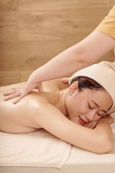 Uśmiechnięta młoda kobieta mająca dzień urody, otrzymuje profesjonalny masaż pleców w salonie spa