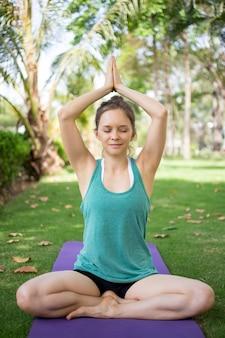 Uśmiechnięta młoda kobieta medytuje w pozycji jogi