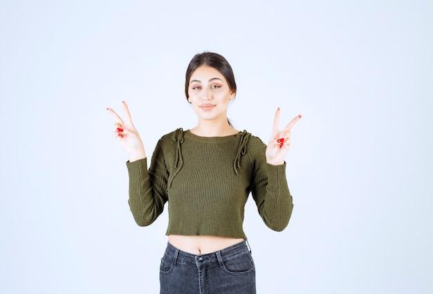 Uśmiechnięta młoda kobieta model stojący i pokazujący znak zwycięstwa.