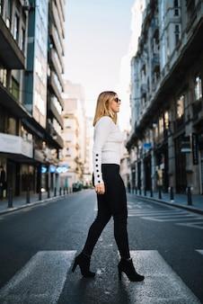 Uśmiechnięta młoda kobieta na drodze w mieście