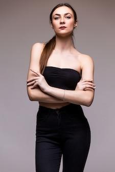 Uśmiechnięta młoda kobieta na szarym pustym studiu