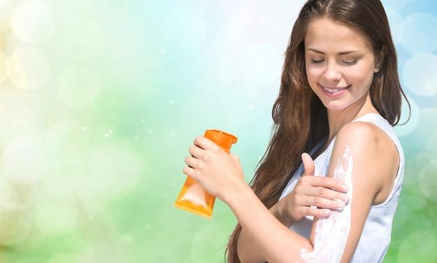 Uśmiechnięta młoda kobieta nakłada krem przeciwsłoneczny na plaży