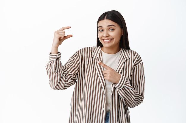 Uśmiechnięta młoda kobieta niezręcznie wskazująca na mały gest, pokazująca drobiazg, maleńki przedmiot w dłoni, stojący na białej ścianie