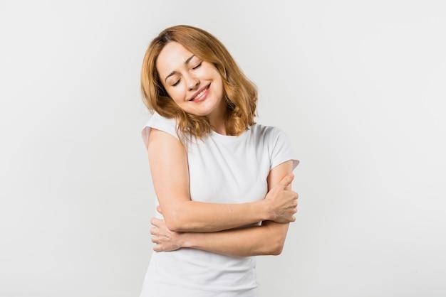 Uśmiechnięta młoda kobieta obejmuje herself przeciw białemu tłu