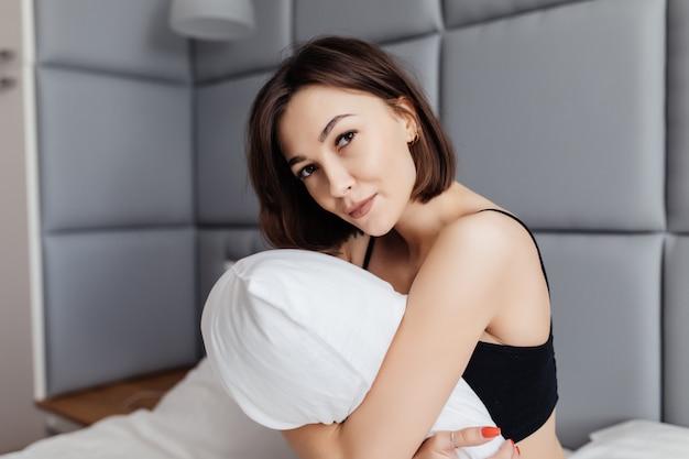 Uśmiechnięta młoda kobieta obejmuje jej poduszkę rankiem w jej sypialni w domu