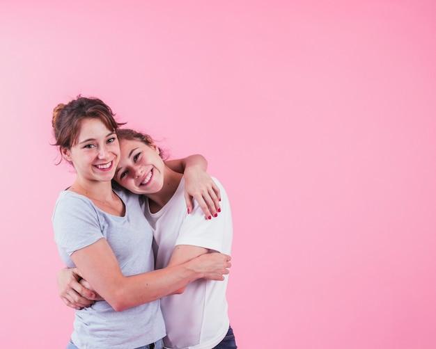 Uśmiechnięta młoda kobieta obejmuje jej siostry przeciw różowemu tłu