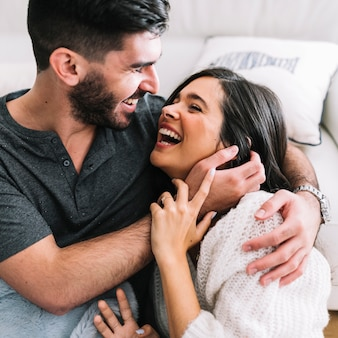 Uśmiechnięta młoda kobieta obejmuje śmiać się