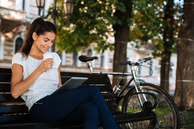 Uśmiechnięta młoda kobieta odpoczywa na ławce przy filiżance kawy i za pomocą tabletu na zewnątrz