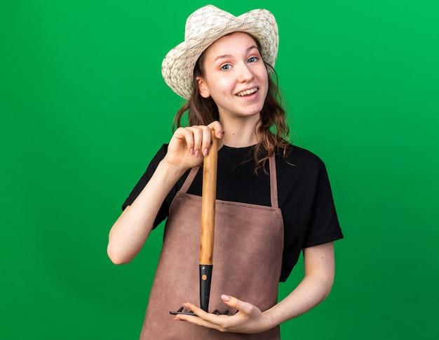 Uśmiechnięta młoda kobieta ogrodniczka w kapeluszu ogrodniczym trzymająca prowizję