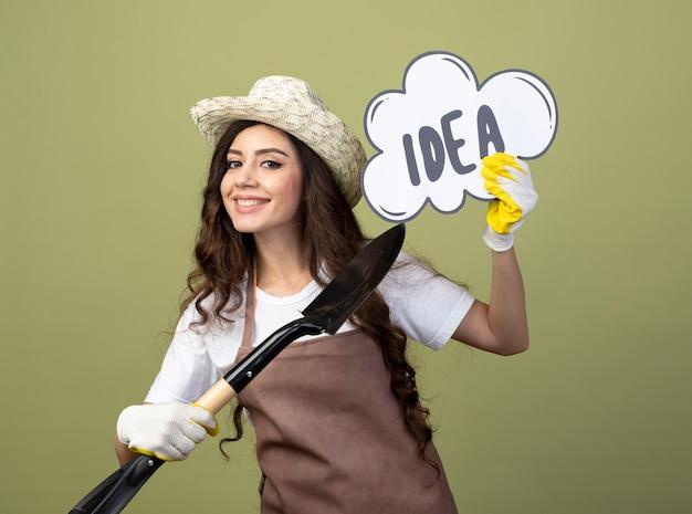 Uśmiechnięta młoda kobieta ogrodniczka w mundurze na sobie kapelusz ogrodniczy i rękawiczki trzyma i wskazuje na bańkę pomysł z łopatą na białym tle na oliwkowej ścianie