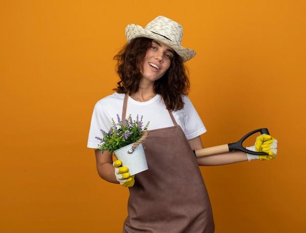 Uśmiechnięta młoda kobieta ogrodniczka w mundurze na sobie kapelusz ogrodniczy i rękawiczki, trzymając kwiat w doniczce i trzymając łopatę w talii