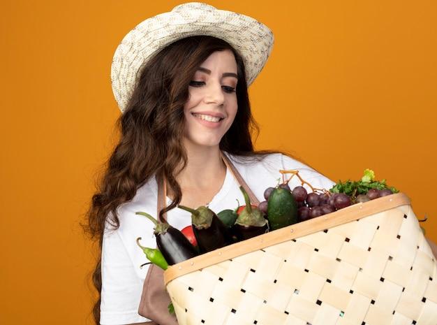 Uśmiechnięta młoda kobieta ogrodnik w mundurze na sobie kapelusz ogrodniczy gospodarstwa i patrząc na kosz warzyw na pomarańczowej ścianie