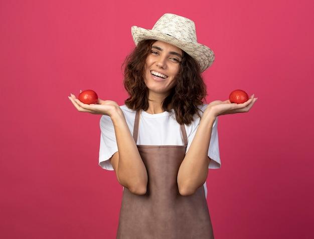 Uśmiechnięta młoda kobieta ogrodnik w mundurze na sobie kapelusz ogrodniczy gospodarstwa pomidory