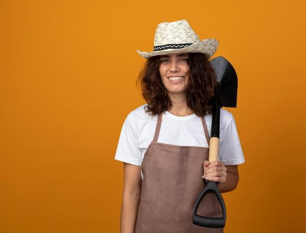 Uśmiechnięta młoda kobieta ogrodnik w mundurze na sobie kapelusz ogrodniczy gospodarstwa umieszczenie łopaty na ramieniu