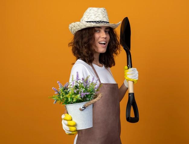 Uśmiechnięta młoda kobieta ogrodnik w mundurze na sobie kapelusz ogrodniczy i rękawiczki trzyma kwiat w doniczce