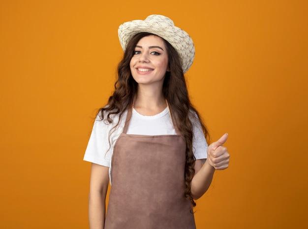 Uśmiechnięta młoda kobieta ogrodnik w mundurze na sobie kapelusz ogrodniczy kciuki do góry na białym tle na pomarańczowej ścianie z miejsca na kopię