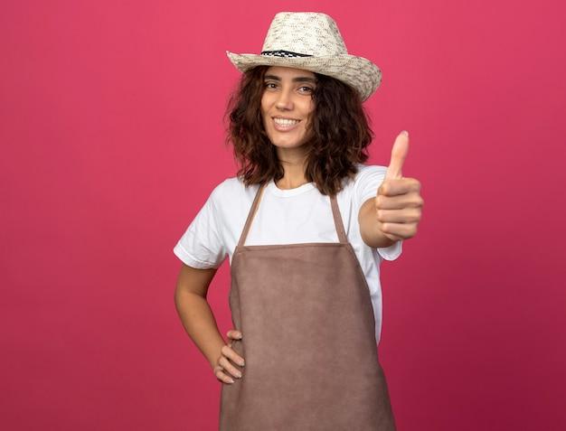 Uśmiechnięta młoda kobieta ogrodnik w mundurze na sobie kapelusz ogrodniczy kładąc rękę na biodrze pokazując kciuk do góry