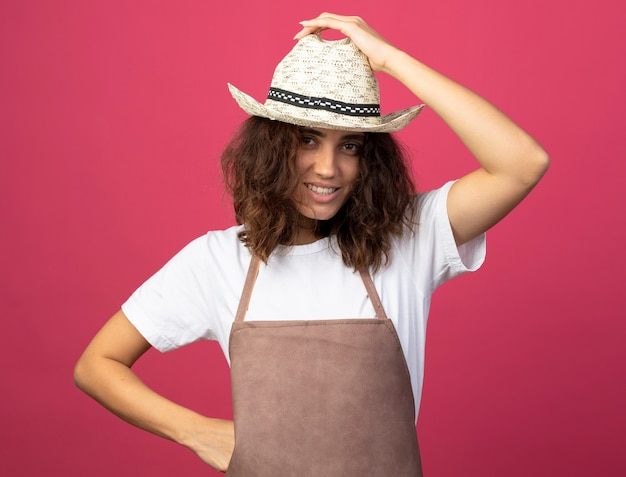 Uśmiechnięta młoda kobieta ogrodnik w mundurze na sobie kapelusz ogrodniczy kładąc rękę na biodrze trzymając kapelusz na różowym tle