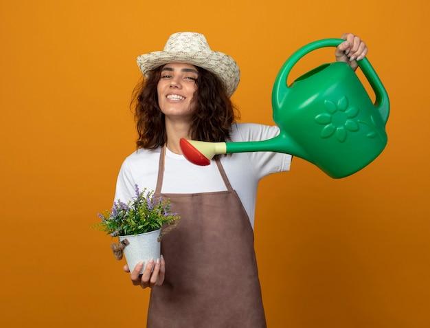 Uśmiechnięta młoda kobieta ogrodnik w mundurze na sobie kapelusz ogrodniczy podlewanie kwiat w doniczce z konewka na białym tle na pomarańczowej ścianie