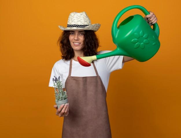 Uśmiechnięta młoda kobieta ogrodnik w mundurze na sobie kapelusz ogrodniczy podlewanie kwiatów w doniczce z konewką