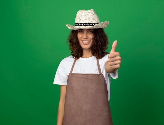 Uśmiechnięta młoda kobieta ogrodnik w mundurze na sobie kapelusz ogrodniczy pokazując kciuk do góry