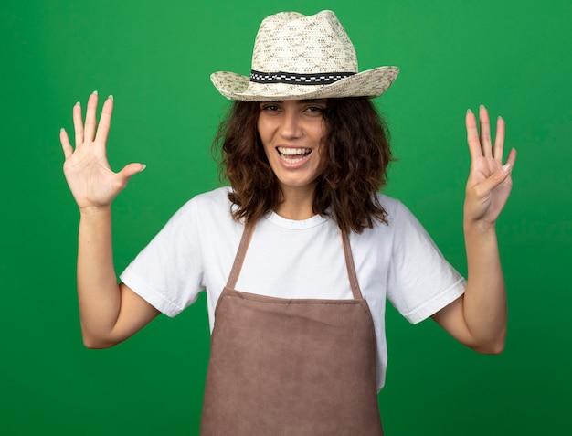 Uśmiechnięta młoda kobieta ogrodnik w mundurze na sobie kapelusz ogrodniczy pokazujący numery differents na białym tle
