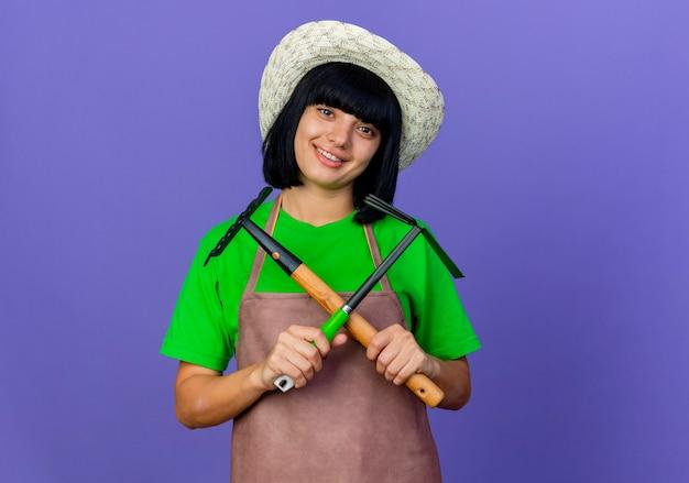 Uśmiechnięta młoda kobieta ogrodnik w mundurze na sobie kapelusz ogrodniczy posiada przechodzenie prowizji i motyka grabie
