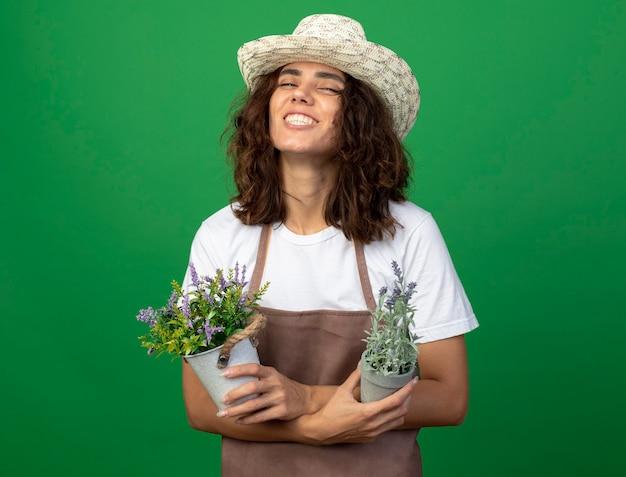 Uśmiechnięta młoda kobieta ogrodnik w mundurze na sobie kapelusz ogrodniczy trzyma i krzyżuje kwiaty w doniczkach na białym tle na zielono