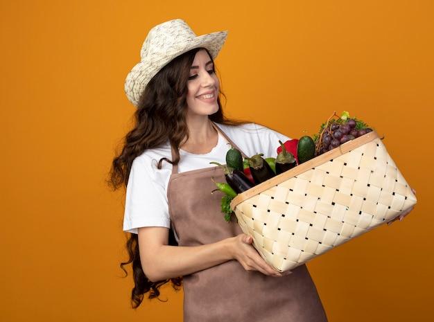 Uśmiechnięta młoda kobieta ogrodnik w mundurze na sobie kapelusz ogrodniczy trzyma i patrzy na kosz warzyw na białym tle na pomarańczowej ścianie z miejsca na kopię