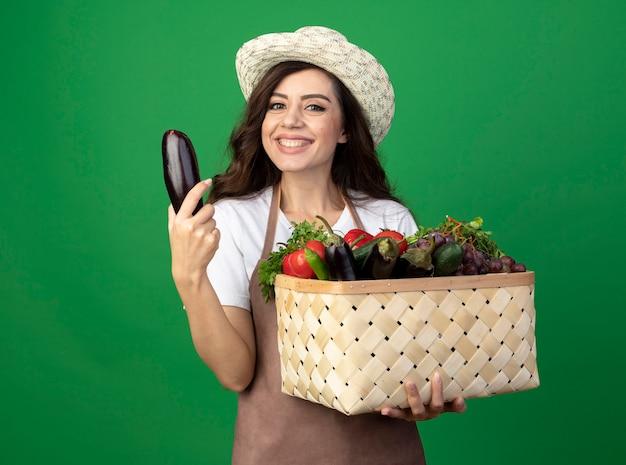Uśmiechnięta młoda kobieta ogrodnik w mundurze na sobie kapelusz ogrodniczy trzyma kosz warzyw i bakłażana na białym tle na zielonej ścianie