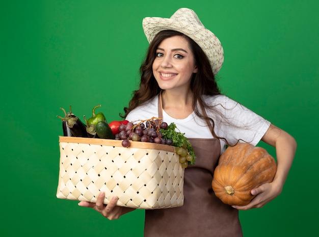 Uśmiechnięta młoda kobieta ogrodnik w mundurze na sobie kapelusz ogrodniczy trzyma kosz warzyw i dyni na białym tle na zielonej ścianie z miejsca na kopię