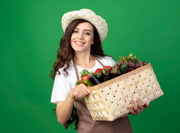 Uśmiechnięta młoda kobieta ogrodnik w mundurze na sobie kapelusz ogrodniczy trzyma kosz warzyw na zielonej ścianie