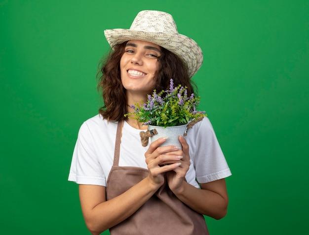 Uśmiechnięta młoda kobieta ogrodnik w mundurze na sobie kapelusz ogrodniczy trzyma kwiat w doniczce na białym tle